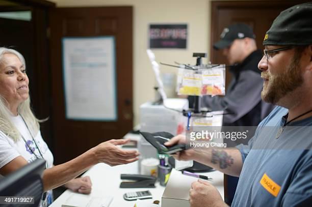 Lorraine Cendejas of Botana Care left helps John Hartlauer of Northglenn purchasing recreational marijuana Northglenn Colorado May 16 2014