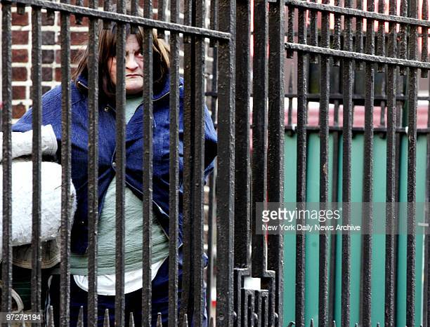 Lorraine House who is homeless looks out through the fence in Lieutenant Petrosino Square Park across from The Falls restaurant and bar where she...