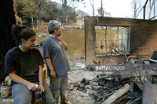 Lorraine Messmer and her daughter Tessa stand in their burnt out home October 28 2003 in Waterman Canyon California Wildfires continue to rage out of...