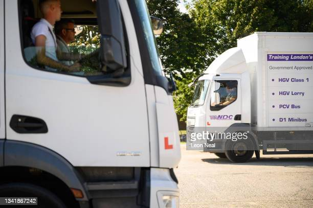Lorries cross paths as students take driving lessons at the NDC heavy goods vehicle training centre on September 22, 2021 in Croydon, England. The...