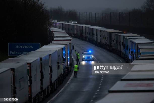 Lorries queue on the M20 on December 21, 2020 in Sellindge, England. Citing concern over a new covid-19 variant and England's surge in cases, France...