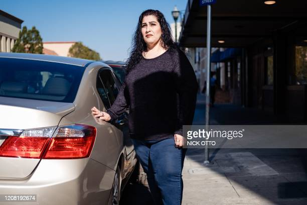 Lorrine Paradela poses next to the car she purchased using some of her monthly cash disbursement in Stockton, California on February 7, 2020. -...