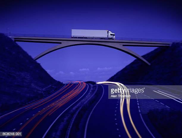 Lorry crossing bridge above motorway, dusk (Digital Composite)