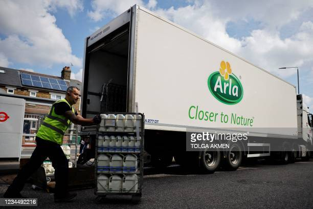 Lorry driver for Arla Foods, a dairy products company makes a milk delivery to a Tesco supermarket in London on August 3, 2021. - Haulage companies...