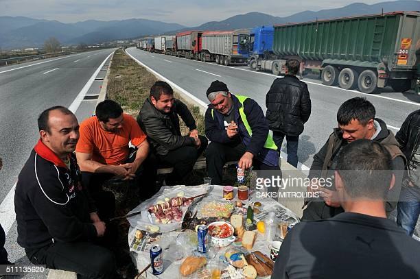 Lorry drivers prepare their meal as they wait next to a column of lorries blocked on a highway near the Promachonas border crossing between Greece...
