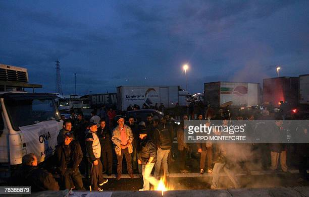 Lorry drivers stand by a fire as they parked their trucks blocking North Rome's motorway 11 December 2007 Italian truck drivers launched a fiveday...