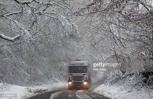 A lorry drives down a road with a line of snow covered trees near Dulverton on January 30 2012 in Exmoor England After unseasonably mild winter...