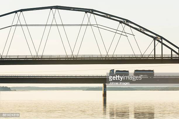 lorry driving through bridge at dusk - norrbotten province stock photos and pictures