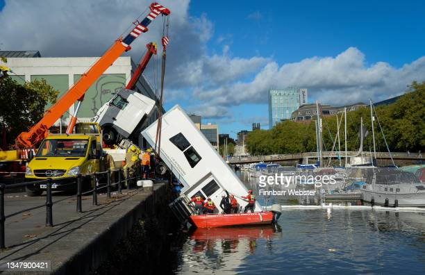 Lorry is recovered from the harbour on October 21, 2021 in Bristol, England. Emergency services were called after a lorry reversed into the harbour...