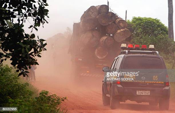 A lorry loaded with confiscated wood is tailed by a Federal Police car on their way to the Maju river in Tailandia Para northen Brazil on February 27...