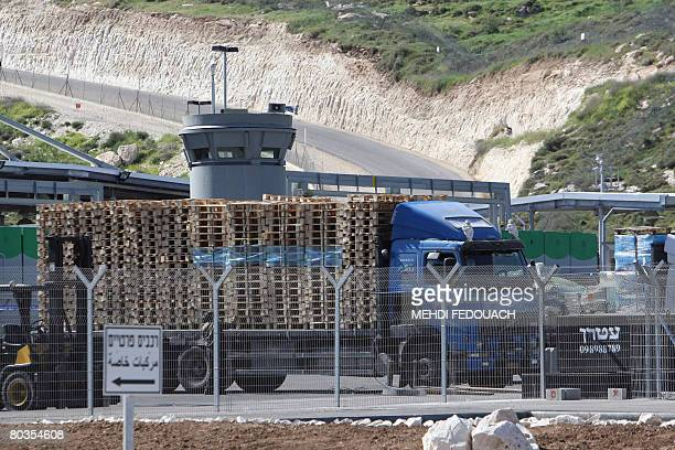 A lorry loaded with pallets passes through the Israeli Tarqumiya checkpoint in the occupied West Bank near the town of Hebron on March 24 2008 As of...