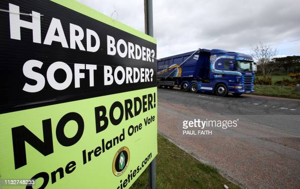A lorry passes a poster by calling for No Border between Ireland and Northern Ireland in a post Brexit United Kingdom in Jonesborough Northern...