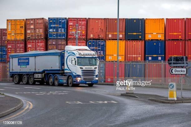 Lorry passes stacked containers in the Belfast Harbour and docks area in Northern Ireland on December 10, 2020. - The port is Northern Ireland's main...