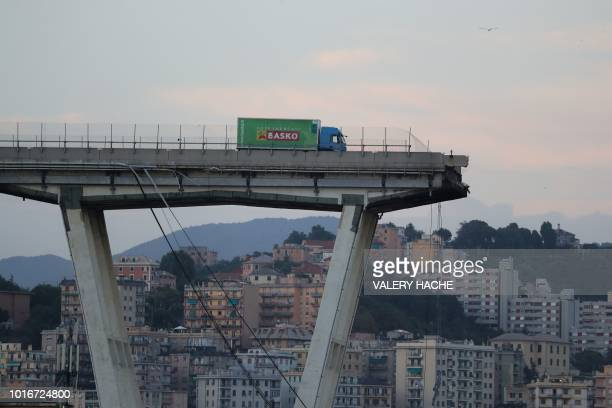 TOPSHOT A lorry stands on the edge of the collapsed Morandi motorway bridge in the northwestern city of Genoa on August 14 2018 About 30 people were...