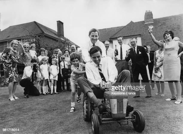 Lors de la fête donnée pour sa victoire à Indianapolis, Graham Hill et son fils Damon Hill poussent le tracteur conduit par Jim Clark à Mill Hill en...