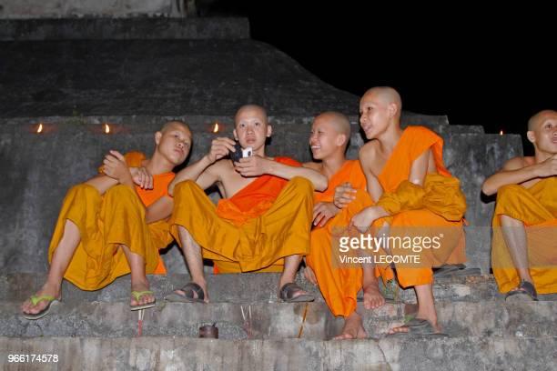 Lors dune cérémonie au cours de la fête des lumières des moines et des novices bouddhistes en tenue traditionnelle sennuient sur les marches de leur...