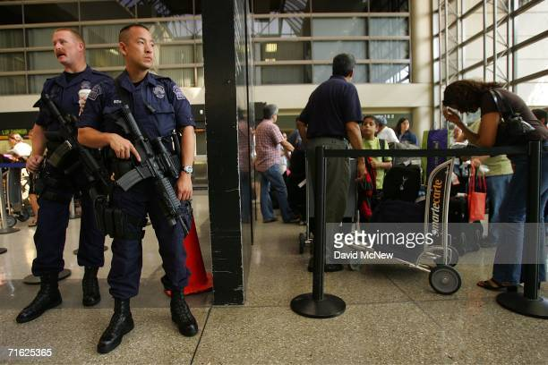 Los Angeles Airport Police officers armed with rifles stand guard as international travelers wait in line in the Bradley International Terminal at...