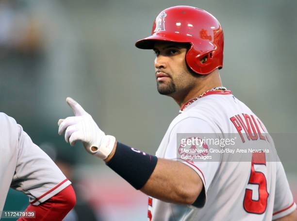 Los Angeles Angels' Albert Pujols signals the teammates in the dugout after connecting an RBI single against the Oakland Athletics in the in the...