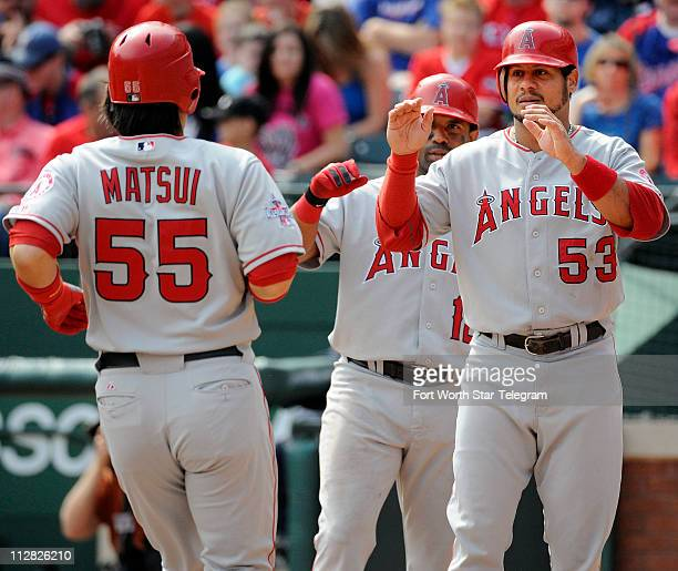 Los Angeles Angels designated hitter Hideki Matsui is welcomed at home plate by Los Angeles Angels right fielder Bobby Abreu after Matsui hit a two...