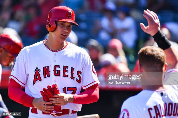 Los Angeles Angels Designated hitter Shohei Ohtani gets a high five after scoring a run during a MLB game between the Seattle Mariners and the Los...