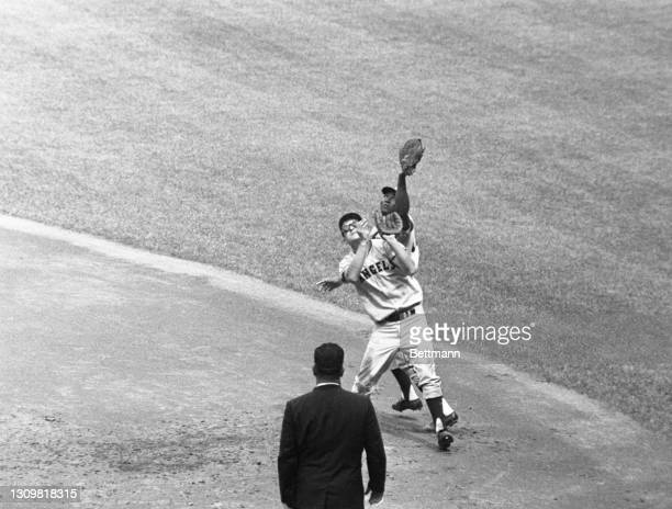 Los Angeles Angel's first baseman Vic Power outreaches second baseman Bobby Knoop to catch Yankees' Joe Pepitone's fly into short right field. The...