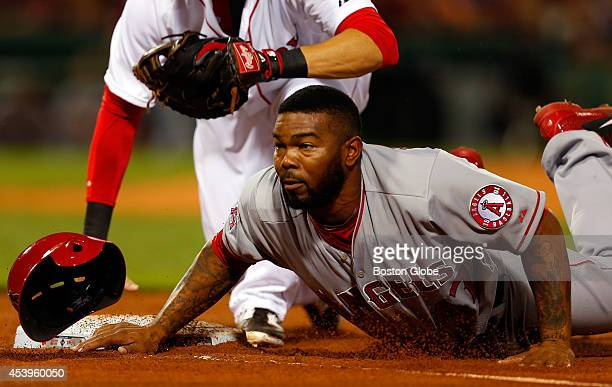 Los Angeles Angels' Howie Kendrick loses his helmet as he is tagged out at first by Boston Red Sox first baseman Kelly Johnson during the third...