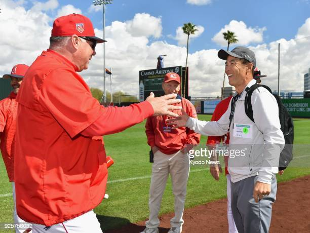 Los Angeles Angels manager Mike Scioscia shakes hands with Shigetoshi Hasegawa a retired Japanese pitcher who used to play for the club at the team's...