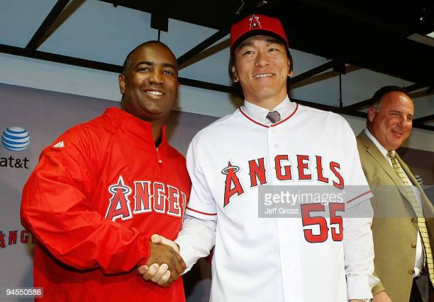 Los Angeles Angels of Anaheim general manager Tony Reagins and Hideki Matsui shake hands as manager Mike Scioscia looks on during a press conference...