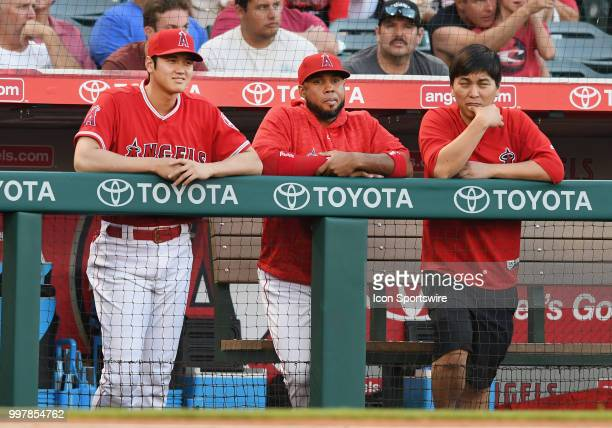 Los Angeles Angels of Anaheim pitcher Shohei Ohtani infielder Luis Valbuena and translator Ippei Mizuhara stand in the dugout during the first inning...