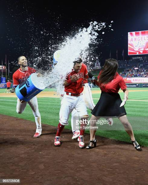 Los Angeles Angels of Anaheim second baseman Ian Kinsler and television host Alex Curry are drenched with water by shortstop Andrelton Simmons on the...