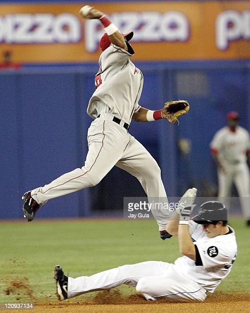 Los Angeles Angels of Anaheim SS Orlando Cabrera jumps high over a sliding Frank Catalanotto of the Blue Jays but was unable to complete the double...