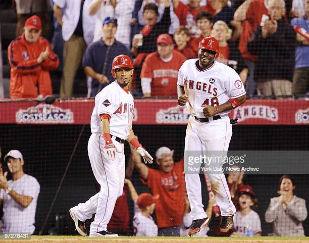 Los Angeles Angels of Anaheim's Maicer Izturis left congratulates Torii Hunter after Hunter scores goahead run in the 7th inning of Game 5 of the...