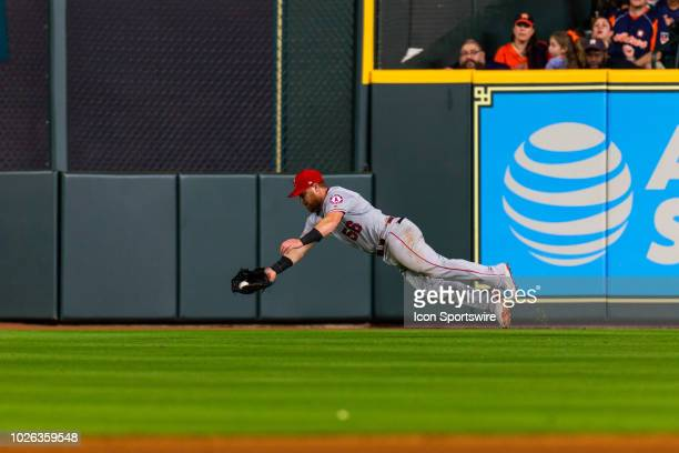 Los Angeles Angels right fielder Kole Calhoun dives making the catch for the out hit by Houston Astros catcher Martin Maldonado in the eighth inning...