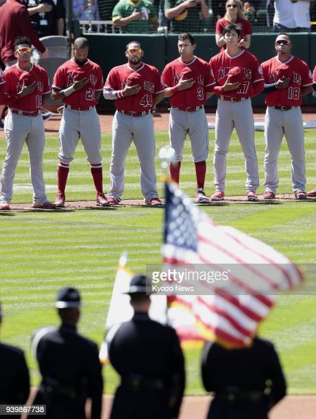 Los Angeles Angels rookie Shohei Ohtani and teammates line up during the national anthem before an Opening Day game against the Oakland Athletics on...