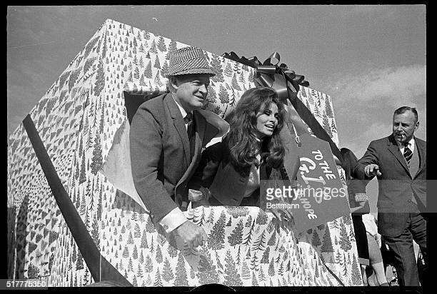 Los Angeles CA Comedian Bob Hope and actress Raquel Welch break through a gaily decorated package labled 'To the GI's' moments before boarding a MATS...