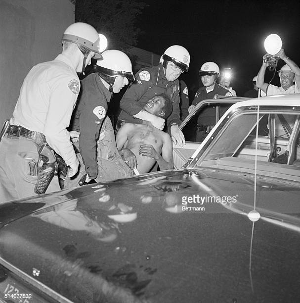 Los Angeles, CA: Policemen force a rioter here into a police car during second night in a row of rioting. The rioters, led by a hard core of 300...