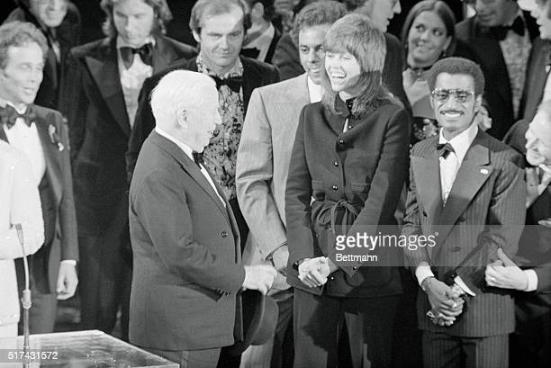 Los Angeles California Comic Charlie Chaplin turns and shakes hands with singer Johnny Mathes as actress Jane Fonda who won the best actress award at...