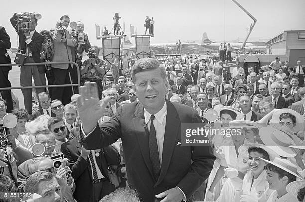 Los Angeles, California: Front running Sen. John F. Kennedy waves to cameraman upon his arrival at International Airport here where he will assume...