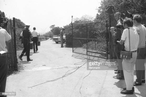 Members of the Los Angeles Police Department crime lab pass by newsmen as they go through the gate that leads to the house where a woman tentatively...