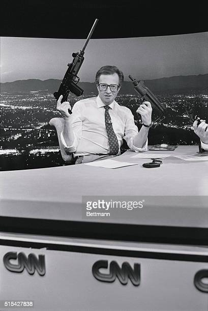 Los Angeles, California: Talk show host Larry king holds up an Uzi machine gun and a replica toy Uzi water gun on his show Larry King Live. King, who...