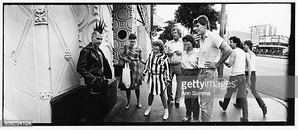 tourists in new wave fashions gawk at a Mohawkwearing punk in full regalia near Hollywood Blvd in the early 1980s