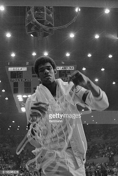 Los Angeles, California: UCLA's Lew Alcindor pulls down the net as a trophy after the UCLA Bruins won the NCAA finals by defeating North Carolina...