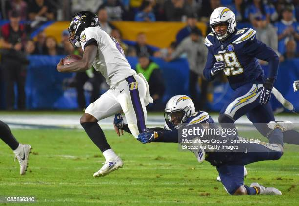 Los Angeles Chargers defensive back Adrian Phillips trips up Baltimore Ravens quarterback Lamar Jackson at the StubHub Center in Carson on Saturday...