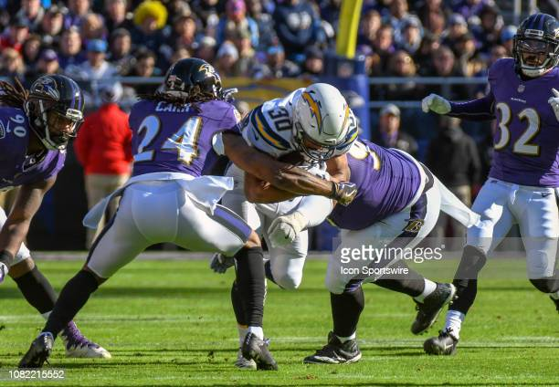 Los Angeles Chargers running back Austin Ekeler is brought down by Baltimore Ravens cornerback Brandon Carr and defensive tackle Michael Pierce on...