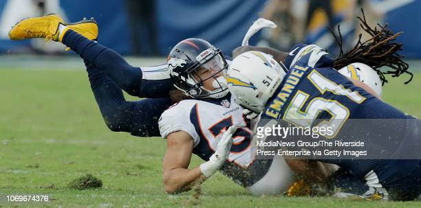 Los Angeles Chargers strong safety Jahleel Addae and Los Angeles Chargers outside linebacker Kyle Emanuel stop Denver Broncos running back Phillip...