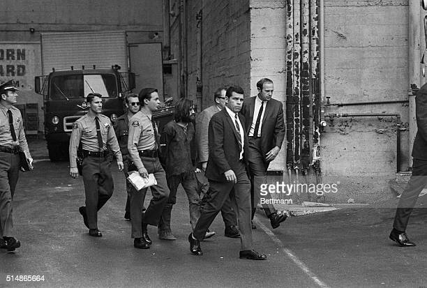Charles Manson accused leader of a hippie cult charged with the TateLaBianca murders is heavily guarded as he leaves the Hall of Justice following...