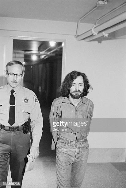 Charles Manson in manacles and escorted by a sheriff's deputy heads for the courtroom as his trial continues for the TateLaBianca murders In court...