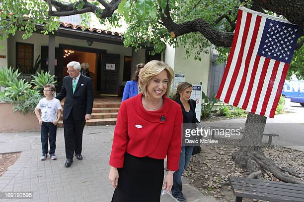 Los Angeles City Controller Wendy Greuel walks from her polling place with her her son Thomas Schramm and husband Dean Schramm after voting in her...