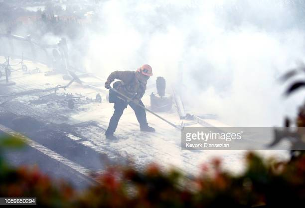 Los Angeles City firefighter puts out a fire on a wood deck behind a house after a Super Scooper firefighting plane made a drop on the house to save...