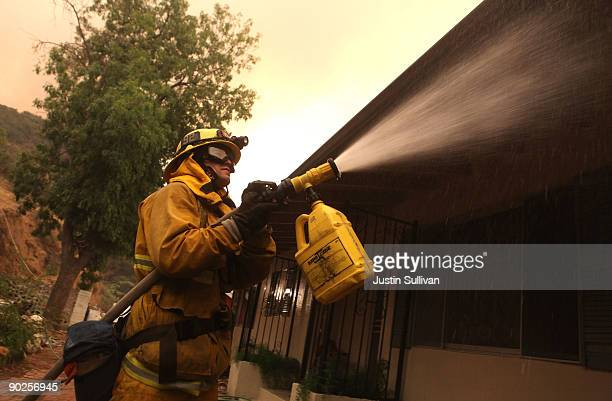 Los Angeles City firefighter sprays foam fire retardant on a home September 1 2009 in Tujunga California The out of control Station Fire has burned...
